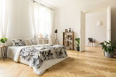 Stylish apartment interior with white walls and herringbone wood. En floor. A view from a bedroom with a big bed to another room with an armchair. Real photo royalty free stock photo