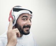 Stylish Arabian man in headphones, Arabian guy listening to musi Stock Image