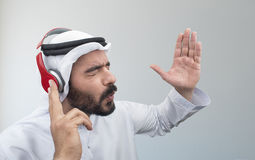 Stylish Arabian man in headphones, Arabian guy listening to music Royalty Free Stock Images