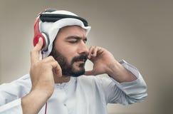Stylish Arabian man in headphones, Arabian guy listening to music.  Stock Images