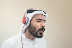 Stylish Arabian man in headphones, Arabian guy listening to music Stock Image