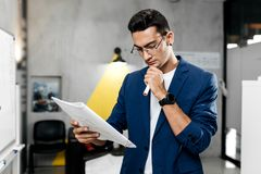 Stylish architect dressed in blue checkered jacket and jeans works with blueprints in the modern office stock photo
