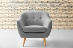 Stylish armchair against brick wall Royalty Free Stock Image