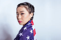 Stylish asian girl wrapped in american flag looking at camera isolated on grey Royalty Free Stock Photos