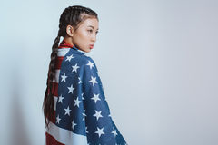 Stylish asian girl wrapped in american flag standing and looking away Stock Images