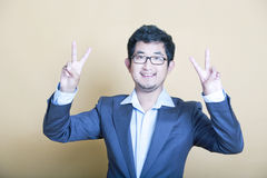 Stylish Asian man making 'peace' symbols Royalty Free Stock Image