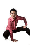 Stylish asian young man squatting. Stylish squatting asian young man in pink shirt Royalty Free Stock Photo
