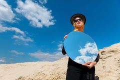 Stylish attractive girl posing with round mirror and reflection of. Cloudy sky royalty free stock photos