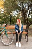 Stylish attractive girl sitting on a bench in a park near a bicycle with a smartphone in his hands, and looking away stock images