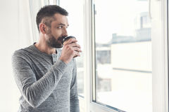 Stylish attractive guy is enjoying hot beverage in office Stock Images