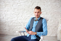 Stylish attractive man sitting in a chair Stock Photography