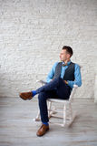Stylish attractive man sitting in a chair Stock Images