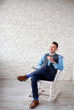 Stylish attractive man sitting in a chair Royalty Free Stock Photo
