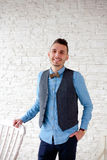 Stylish attractive man standing by chair Royalty Free Stock Images