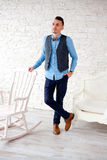 Stylish attractive man standing by chair Royalty Free Stock Photos