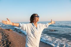 Stylish attractive mature woman 50-60 with open arms on the seas. Hore, travel and retirement, fashion and beauty, active elderly people Stock Photography