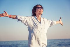 Stylish attractive mature woman 50-60 with open arms on the seas. Hore, travel and retirement, fashion and beauty, active elderly people Stock Photos