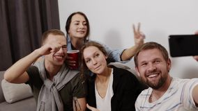 Stylish, attractive, modern positive friends sitting in living room, having cups and bottles in hands, shooting selfie. On smart phone, laughing, showing stock footage