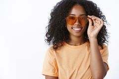 Stylish attractive modern urban trendy dark-skinned girl wearing cool sunglasses smiling delighted ready sunbathing near royalty free stock images