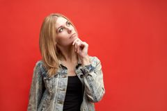Stylish attractive slender young blonde student woman thoughtfully holds her chin and looks up with a pensive expression. royalty free stock image