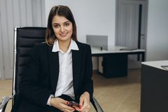 Stylish attractive young businesswoman with a lovely smile sitting in front of a table in the office grinning at the camera stock photo