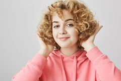Stylish attractive young european woman with curly blonde hair touching haircut while smiling and being pleased with her. Appearance, standing over gray Royalty Free Stock Image