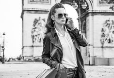 Fashion-monger near Arc de Triomphe in Paris using mobile phone Stock Images