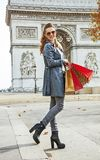 Happy trendy woman in trench coat shopping in Paris, France. Stylish autumn in Paris. Full length portrait of happy trendy woman in trench coat with shopping Stock Photography