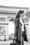 Pensive modern woman near Arc de Triomphe in Paris, France. Stylish autumn in Paris. pensive modern woman in trench coat near Arc de Triomphe in Paris, France Royalty Free Stock Photo