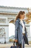 Pensive modern woman near Arc de Triomphe in Paris, France. Stylish autumn in Paris. pensive modern woman in trench coat near Arc de Triomphe in Paris, France Royalty Free Stock Photos