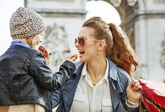 Mother and daughter near Arc de Triomphe eating macaroons. Stylish autumn in Paris. smiling young mother and daughter with shopping bags near Arc de Triomphe in Royalty Free Stock Image