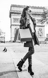 Woman shopper near Arc de Triomphe having coffee and macaroon. Stylish autumn in Paris. trendy woman in trench coat near Arc de Triomphe in Paris, France with Stock Image
