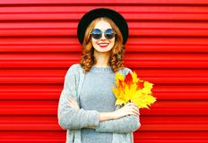 Stylish autumn woman holds yellow maple leaves on a red Royalty Free Stock Photo
