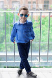 Stylish baby boy with dark hair in blue shirt and in trendy sung Royalty Free Stock Photos