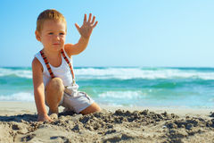 Stylish baby boy waving hand on the beach Royalty Free Stock Photo