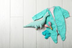 Stylish baby clothes and toys on wooden background, top view. Space for text royalty free stock photography