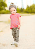 Stylish baby girl walking outdoors Royalty Free Stock Images