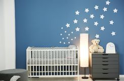 Stylish baby room interior with crib stock image