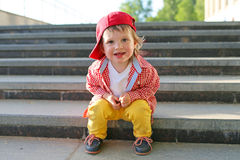 Stylish baby sitting on stairs in summer Royalty Free Stock Photo