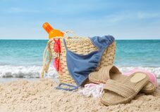 Stylish bag with different accessories on sandy beach near ocean