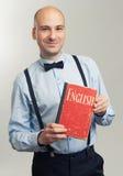 Stylish bald man holding an English textbook Stock Photo