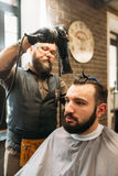 Stylish barber drying mans hair in barbershop Royalty Free Stock Photography