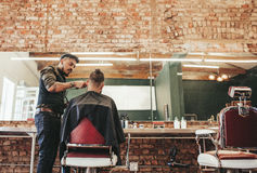 Stylish barber giving haircut to client. At his shop. Hairdresser cutting hair of men sitting in chair at salon Stock Photos