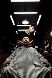 The stylish barbershop. The fashion barber tidies up beard of brutal man sitting in the armchair stock photos