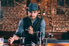 Stylish barman adding cocktail ingredients on whiskey cocktails on bar counter stock image