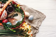 Stylish basket with painted eggs, bread, ham,beets, butter on ru Royalty Free Stock Image