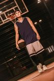 Stylish basketball player. Full length portrait of stylish young basketball player in cap standing with a ball on basketball court outdoors at night royalty free stock photos