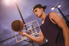 Stylish basketball player. Stylish young basketball player in cap is spinning a ball on his finger while standing on basketball court outdoors in the evening Royalty Free Stock Photos