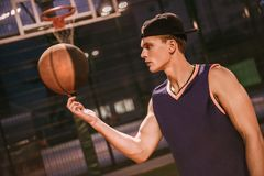 Stylish basketball player. Stylish young basketball player in cap is spinning a ball on his finger while standing on basketball court outdoors in the evening Stock Images