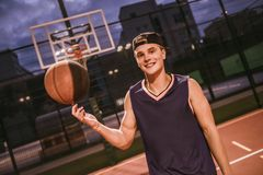 Stylish basketball player. Stylish young basketball player in cap is spinning a ball on his finger while standing on basketball court outdoors in the evening Stock Photography